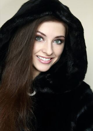 Beautiful smiling woman in new fur black fashion coat looking happy  Closeup portrait photo