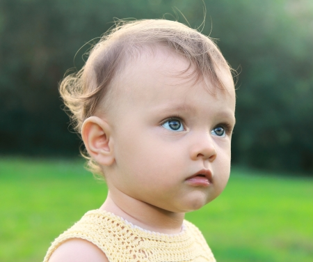 Serious fun baby girl on nature green background thinking looking with interest  Closeup portrait Stock Photo - 15175845