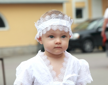 Serious baby girl in white hat outdoors on street background looking  Closeup portrait photo