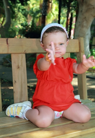 Fun sad baby girl sitting on bench and unhappy holding hands outdoors on park background Stock Photo - 15396897