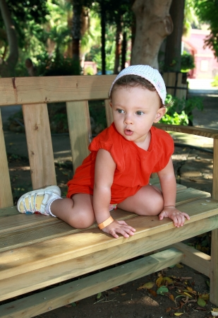 Fun baby sitting on bench with surprising looking face in beautiful park outdoors Stock Photo - 15396898