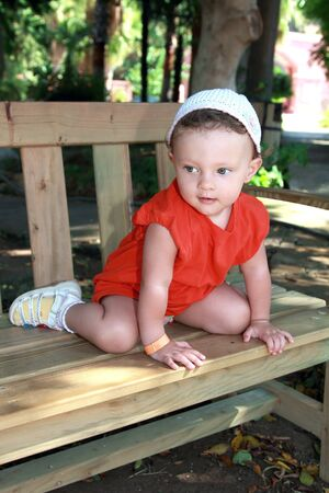 Fun baby girl in hat sitting on bench and looking with interest in summer park outdoors background Stock Photo - 15413364