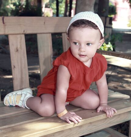 Art portrait of baby sitting on bench in summer park and looking with interest outdoors background Stock Photo - 15413360