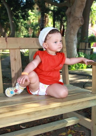 Serious thinking baby girl in hat sitting on bench in beautiful garden outdoors background Stock Photo - 15413363