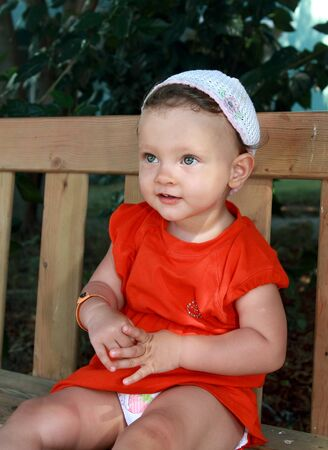 Smiling baby girl in hat portrait sitting on bench outdoor summer background Stock Photo - 15470347