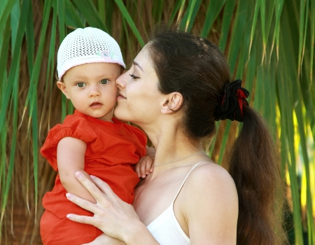 Beautiful mother kissing fun baby girl in hat outdoors green trees background photo