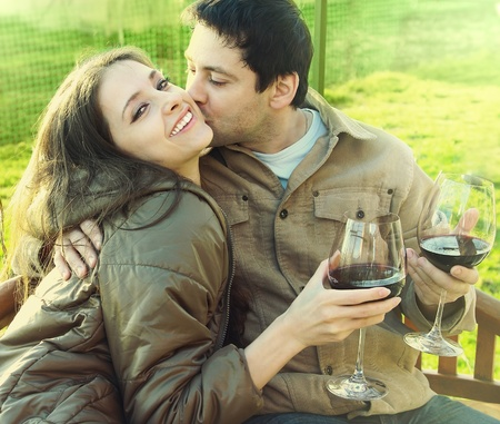 Happy couple drinking red wine outdoor  Man kissing laughing beautiful girl with long hair  She is looking in camera  Closeup bright portrait of happiness and leisure with drink in sunny autumn day photo