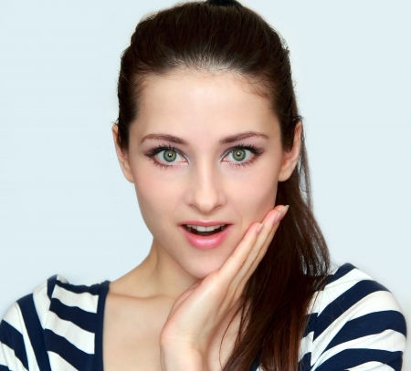 Surprised woman with opened mouth and hand at face looking photo