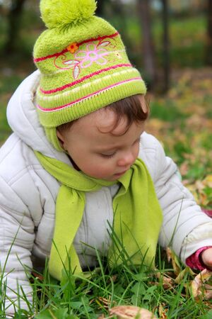 Closeup portrait of baby in hat lying on grass on autumn background outdoors Stock Photo - 15880491