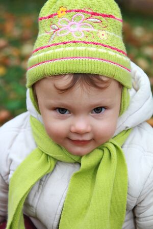Closeup portrait of baby girl in fun hat looking and smiling on autumn backgound Stock Photo - 15880495