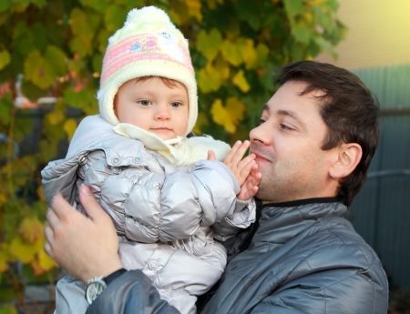 Happy father holding baby in hat and looking with love on yellow autumn background  Closeup family portrait Stock Photo - 15880489