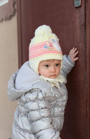 Thinking baby in hat knocking at house door wanting to home and looking serious Stock Photo - 15880485