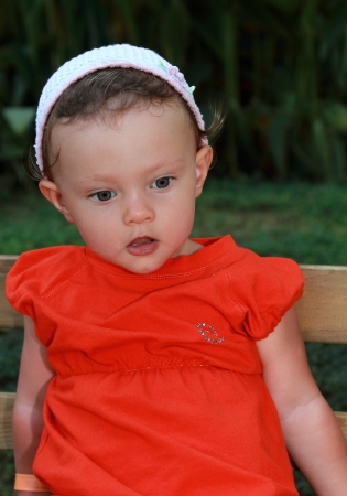 Surprised baby girl sitting on bench with opened mouth and looking in green park outdoors Stock Photo - 15880486