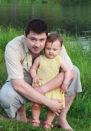 Smiling father holding baby girl outdoors lake and summer grass background  Happy love family Stock Photo - 15880492