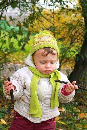 Fun baby girl in hat looking on branches on yellow autumn nature background with pout lips and serious thinking face Stock Photo - 15930529