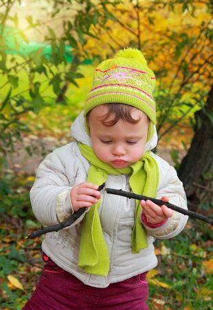 Fun baby looking on branch holding in hands in hat and scarf outdoors autumn yellow background Stock Photo - 15971260