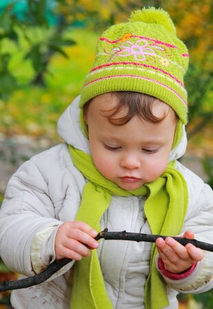 Serious baby looking with interest on branch in fun hat on autumn color background  Closeup portrait Stock Photo - 15971259
