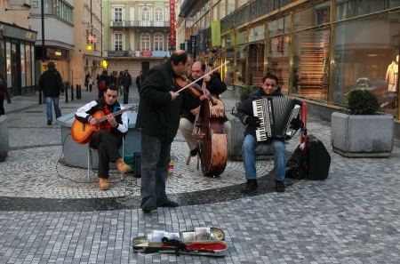 PRAGUE - NOVEMBER 19: Unknown people playing traditional czech music on the old town street on November 19, 2012 in Prague, Czech Republic. To attract tourists to the city the government of Prague allow this.