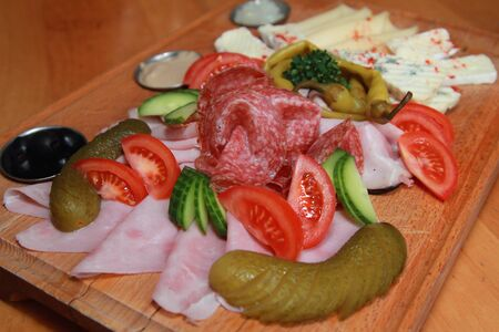 Cheese and salami platter with vegetable and salt cucumber on wooden board photo