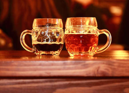 Two beer glasses on wooden table in bar  Dark and lager tasty beer photo