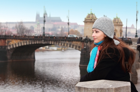 Thinking beautiful woman looking on Prague bridge autumn background  Walking girl in hat and colorful sharf Stock Photo