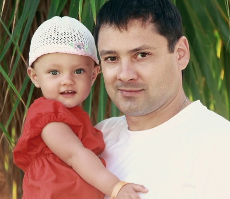 Father and happy baby girl on nature green background  Closeup portrait of love family Stock Photo - 17057133