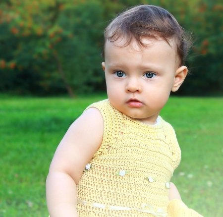 Baby girl on summer green day background outdoors  Fun serious portrait Stock Photo - 17057132