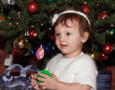 Smiling baby at fir christmas tree holding gift with happy look Stock Photo - 17156164