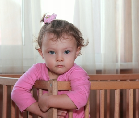 Serious baby girl in crib with thinking look in pink dress  Closeup portrait Stock Photo - 17156160