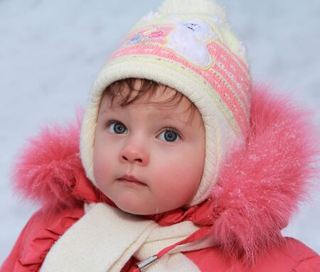 Winter baby girl in hat looking blue fun eyes in red coat  Closeup portrait Stock Photo - 17156161