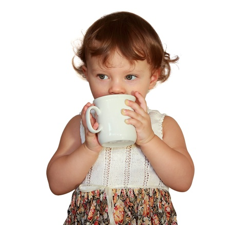 Baby girl drinking from cup water and looking isolated on white background Stock Photo - 17536892