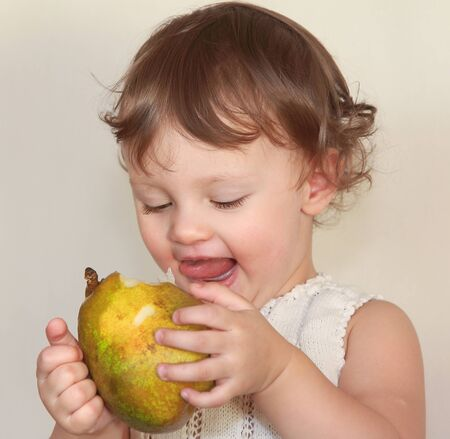 Happy baby eating big pear with joy face  Closeup portrait Stock Photo - 17536887