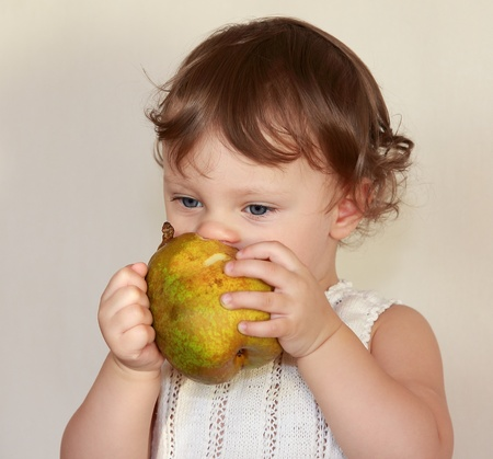 Baby eating fruit pear isolated on white background  Healthy food Stock Photo - 17536890