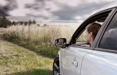 Woman driving car and looking on nature dark blue sky background  Art color portrait photo