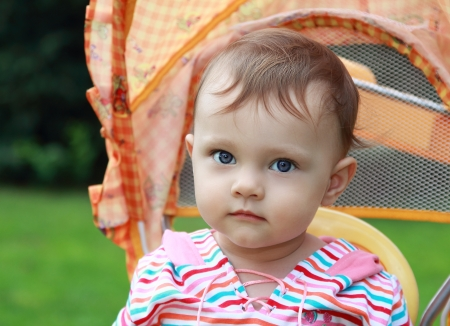 Baby girl in stroller looking outdoors summer green background  Closeup portrait Stock Photo - 17792865