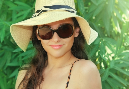 Beautiful woman in hat and sun glasses relaxing on summer holidays photo