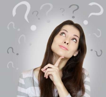 confused woman: Beautiful girl with questions thinks above her head looking up isolated on grey background