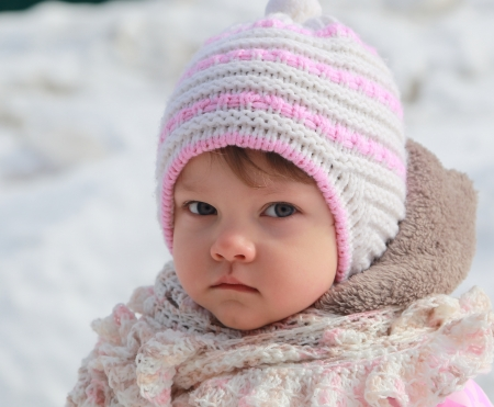 pink hat: Portrait of baby girl in hat on snow winter background  Closeup Stock Photo