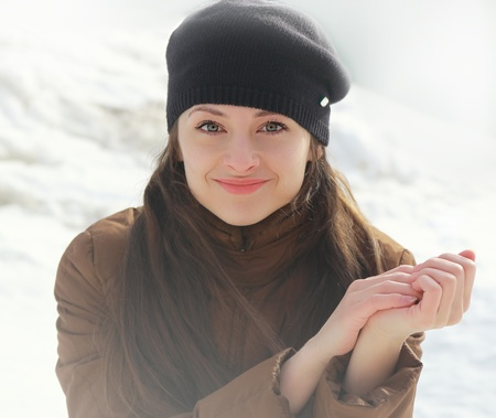 Young smiling woman winter portrait looking happy on snow background photo