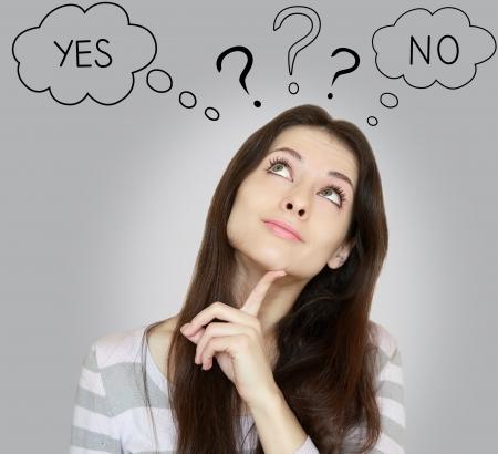 Myślenie młoda kobieta z tak lub nie wybór patrząc z palcem w twarz na szarym tle