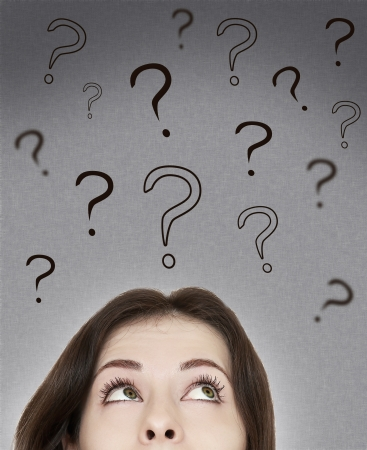 Beautiful thinking woman looking on questions marks above her head on grey background photo