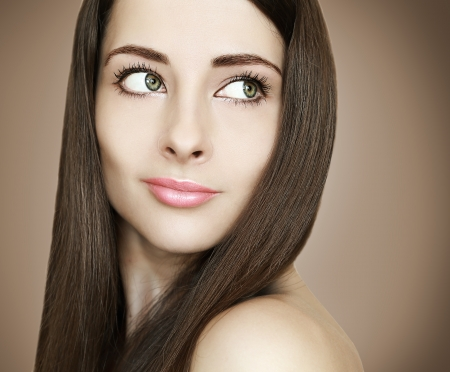 Art portrait of beautiful woman with smooth healthy hair looking on brown background photo