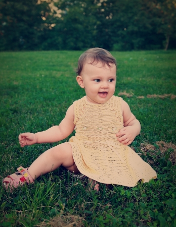 Happy baby girl sitting on green grass on nature summer background  Vintage portrait Stock Photo - 18793357