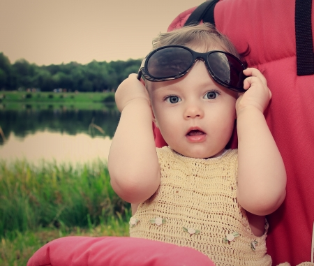 Surprising baby girl holding sunglasses outdoors summer background  Closeup vintage art portrait Stock Photo - 18824366