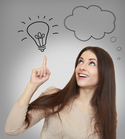Thinking happy woman showing on idea bulb with empty bubble above on grey background Stock Photo - 18969173