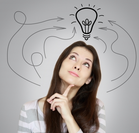 above head: Thinking young woman with arrows and light idea bulb above head on grey background Stock Photo