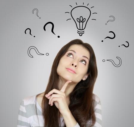 preguntando: Mujer joven de pensamiento con un sí o ninguna opción mirando hacia arriba con el dedo a la cara sobre fondo gris