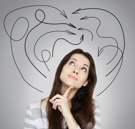 dudas: Mujer joven que piensa y que mira para arriba con muchas flechas por encima de la cabeza en el fondo gris