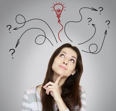 Mujer de pensamiento toma de decisiones y tener una idea de ella mirando hacia arriba sobre fondo gris