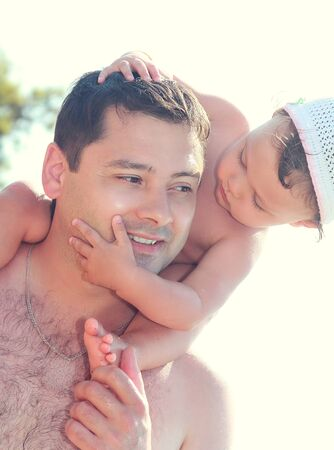 Smiling father holding baby girl on shoulders on summer holidays  Closeup portrait Stock Photo - 19249890